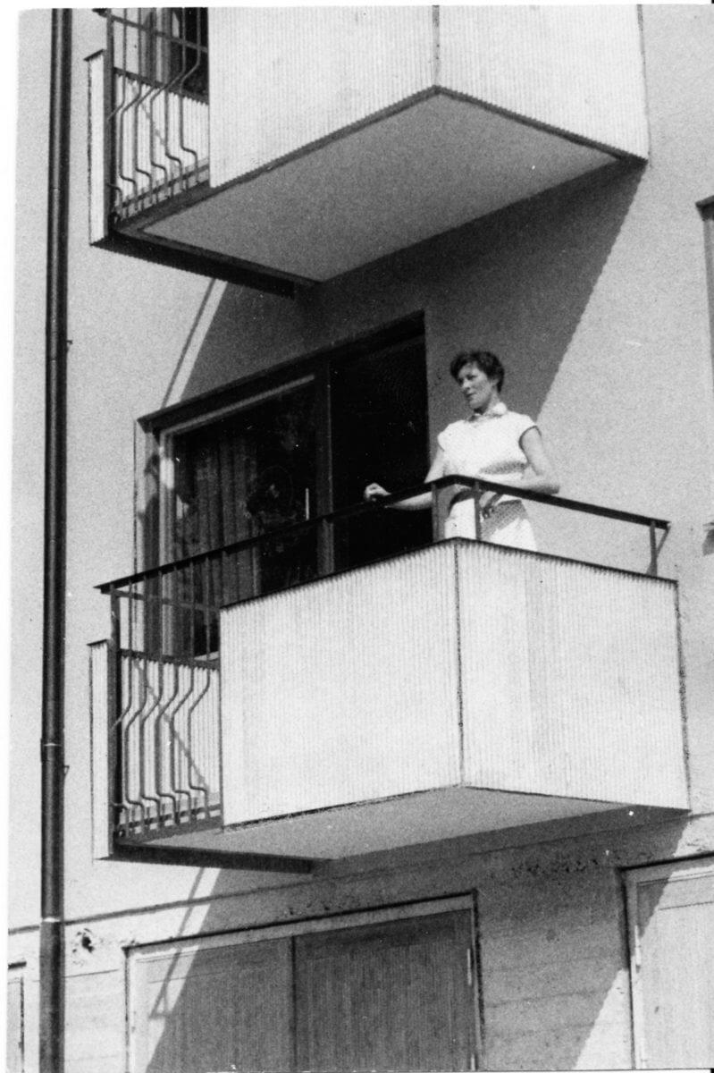 En kvinna står i solljuset på en balkong.