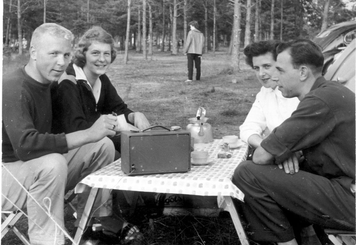 Fyra personer fikar runt ett fällbord och lyssnar på radio.