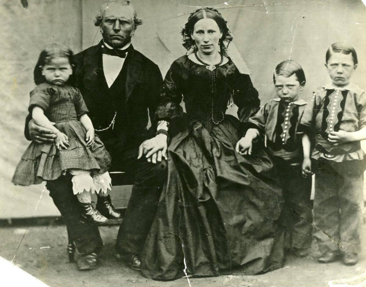 Ett familjefoto där endast kvinnan ser glad ut och de övriga visar upp sura miner.
