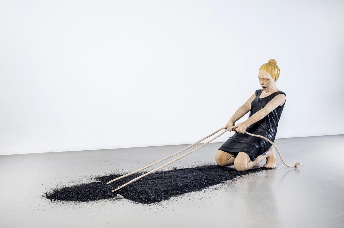 En träskulptur från Yaşam Şaşmazers utställning Metanoia föreställande en kvinna som försöker dra upp sig egen skugga från marken med ett rep.