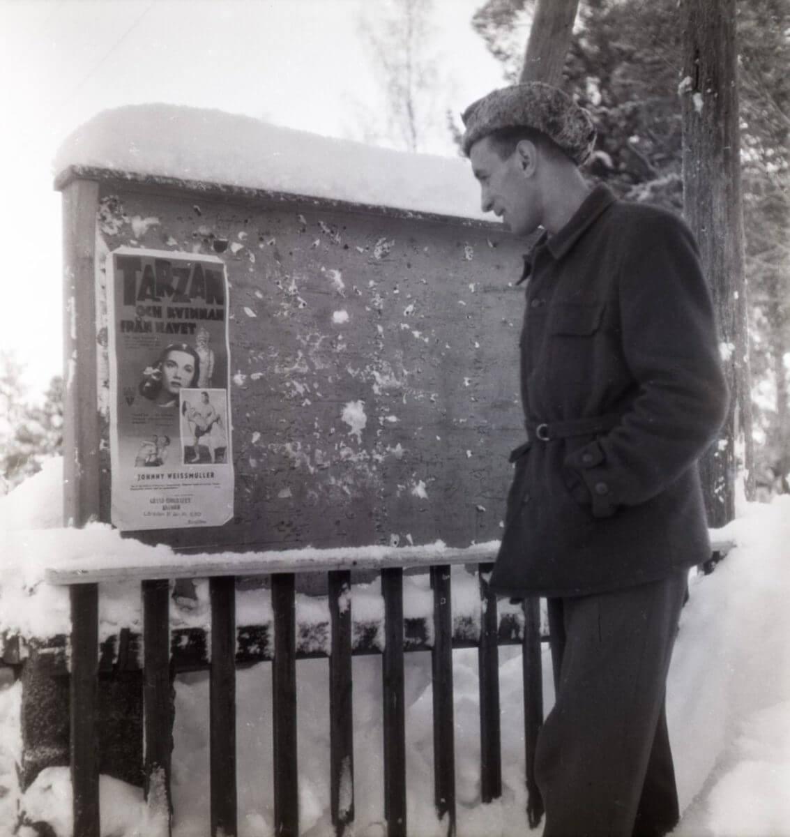 En man står vid en anslagstavla och tittar på en affisch.