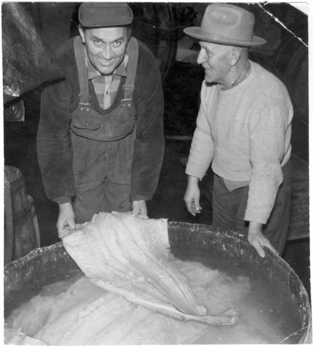 Två män lutar fisk i en tunna.