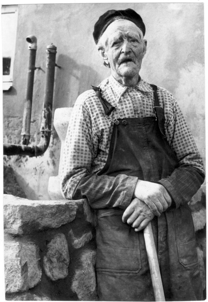 En tandlös man står intill en stenmur och håller ett redskap i sina händer.