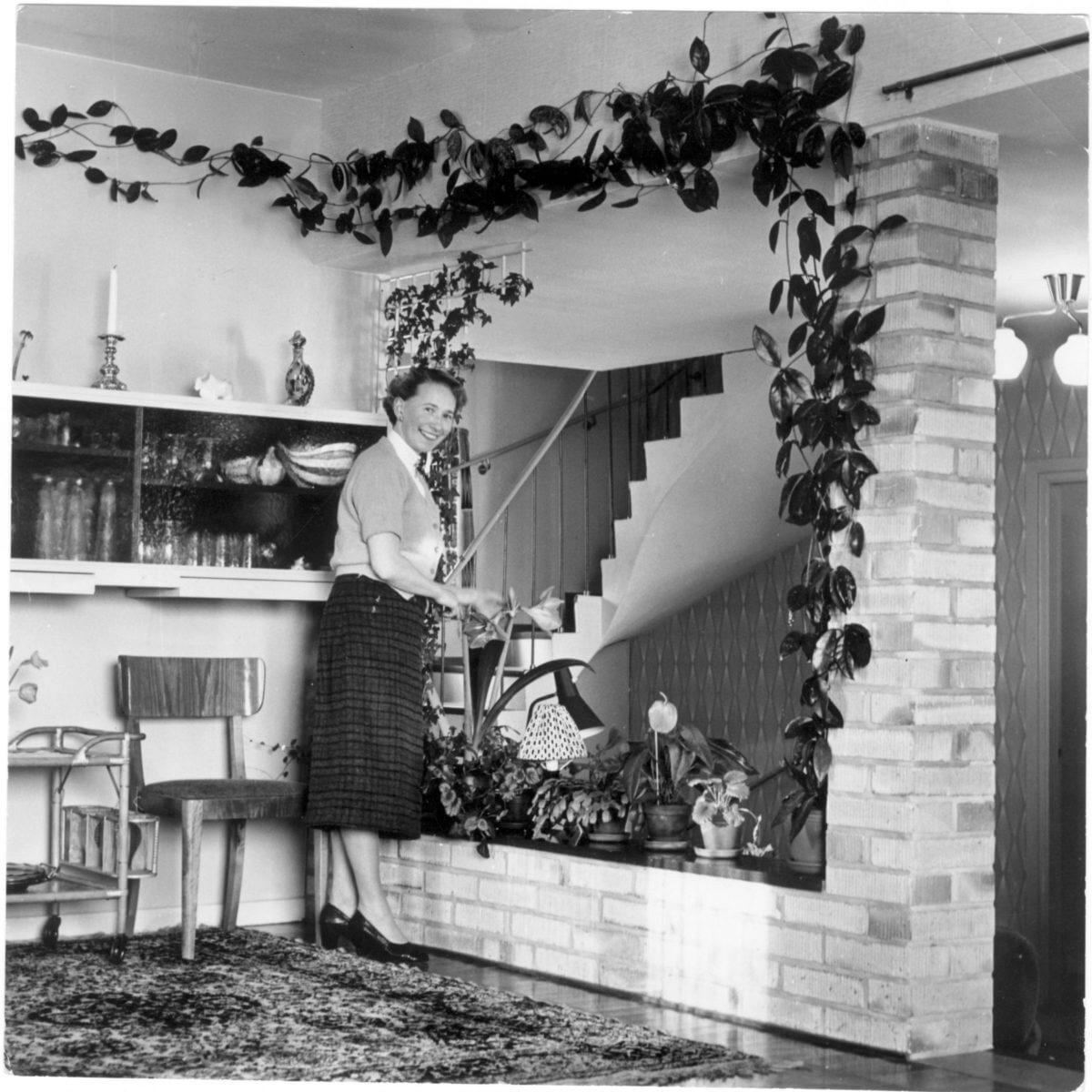 En kvinna ordnar blommorna i sitt hem.