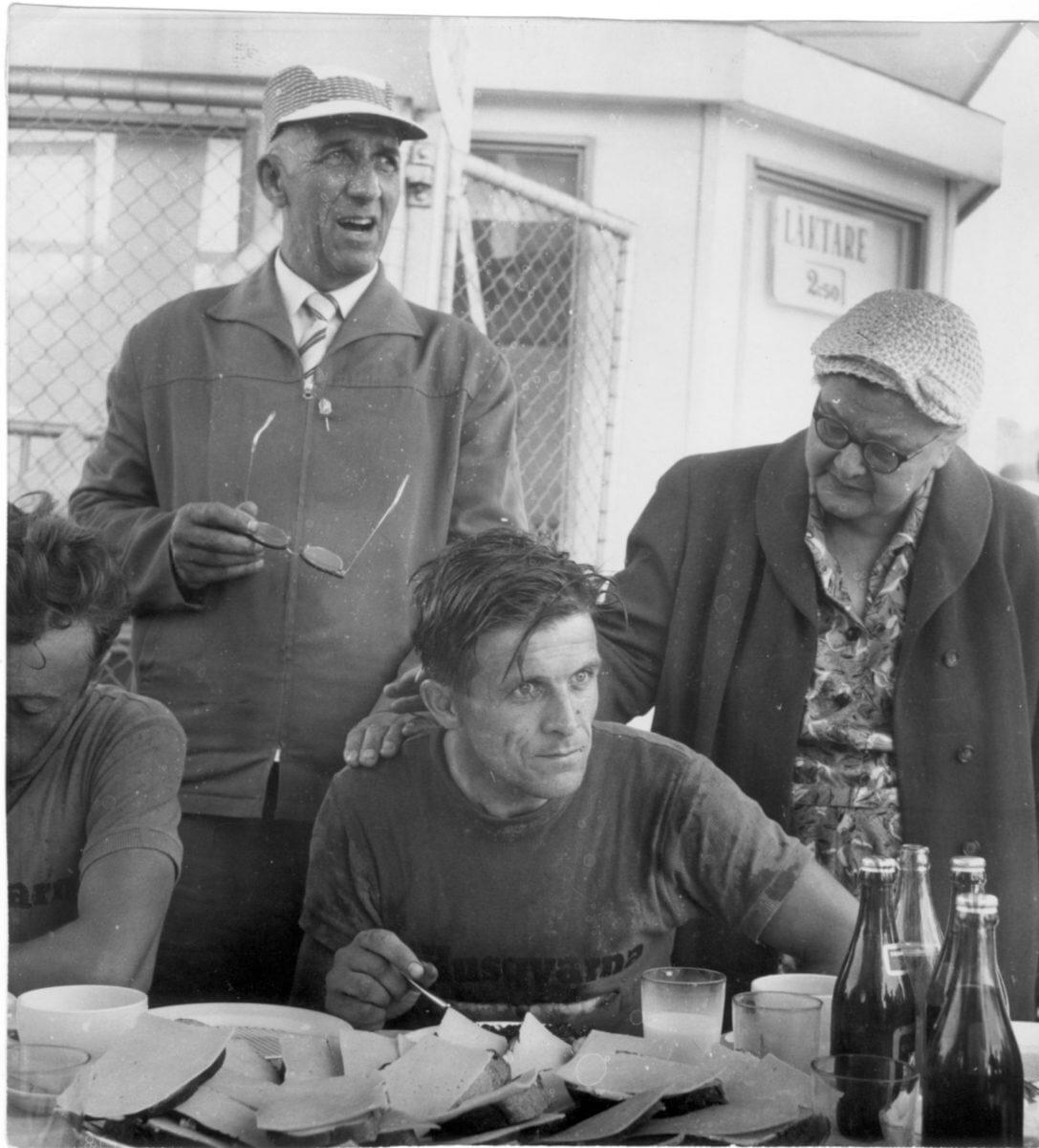 En fokuserad man sitter ned och äter mat framför sina föräldrar.