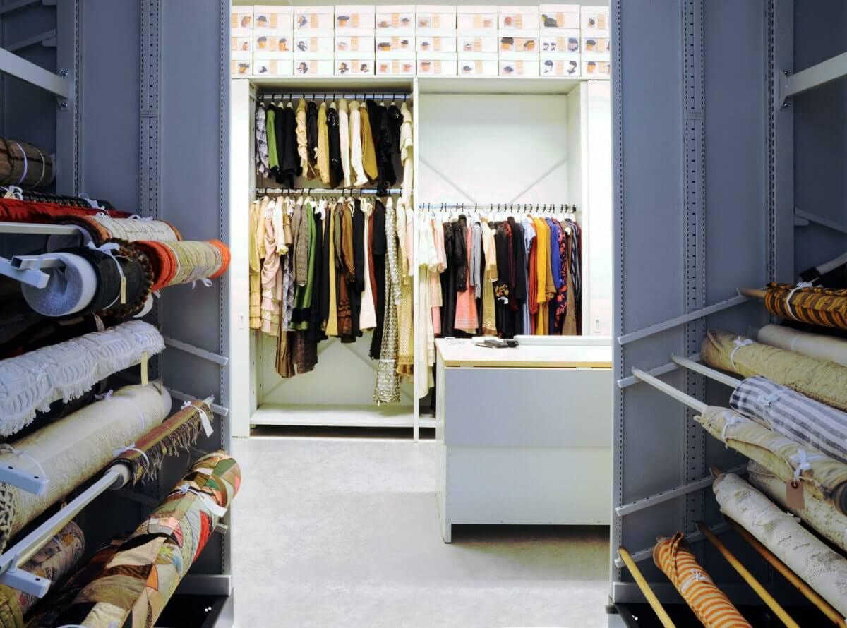 Visningsmagasin för textilföremål vid Hälsinglands museum. I magasinet hänger kläder på galgar, tyger är upprullade samt hattar ligger i lådor.