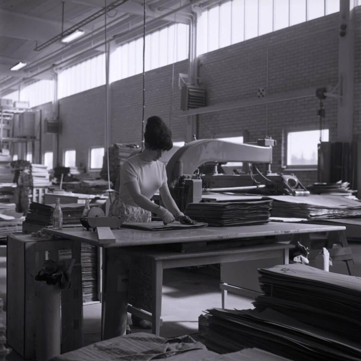 En kvinna arbetar i en träindustrilokal.