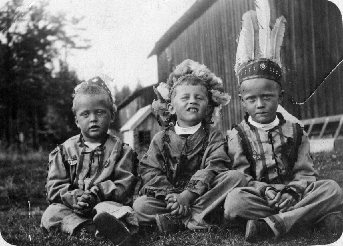 Tre pojkar utklädda till indianer sitter i gräset.