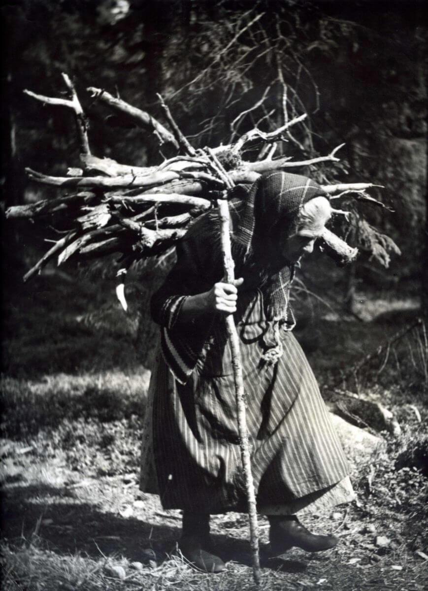 En äldre kvinna bär ved på ryggen och stödjer sig på en pinne med ena handen.