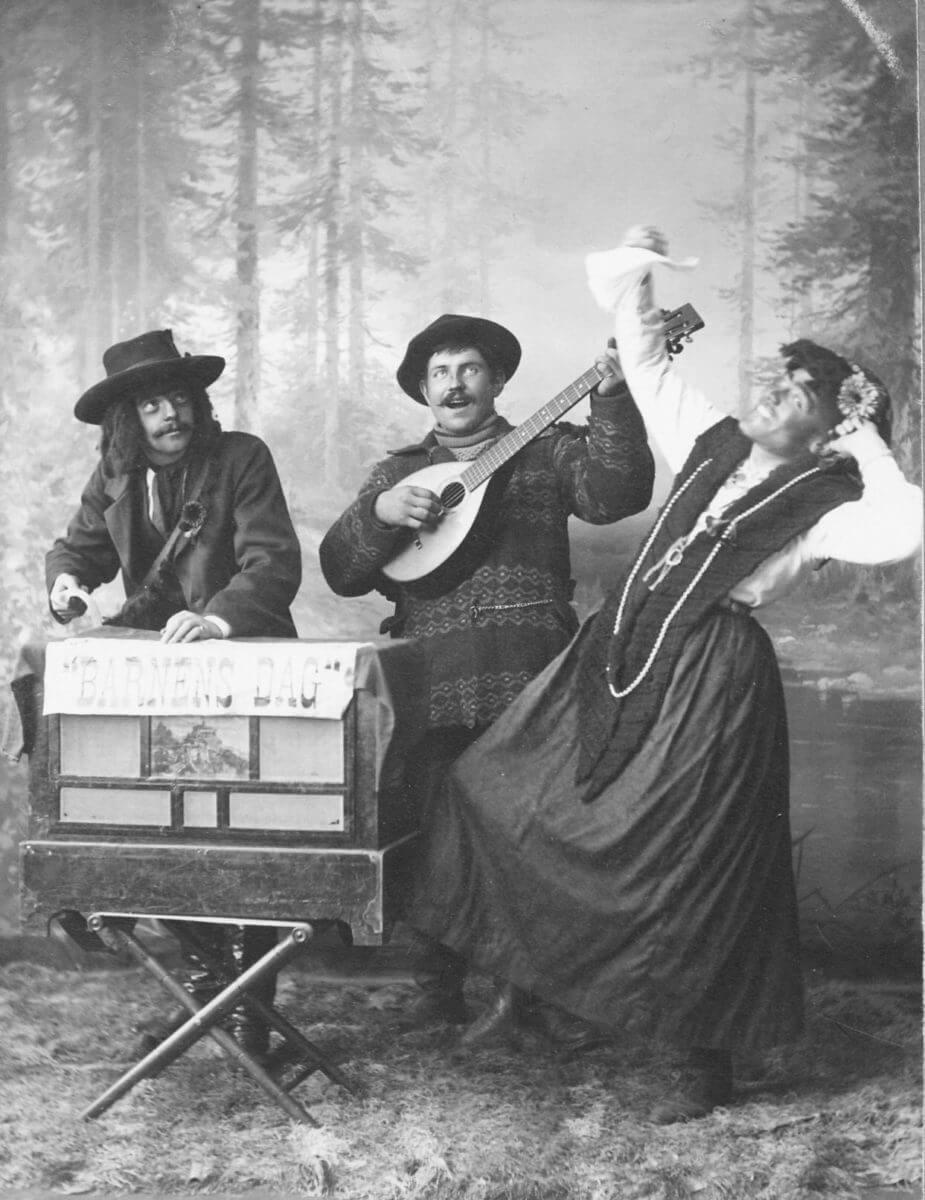 Ett musikuppträdande vid Barnens dag med tre utklädda personer.