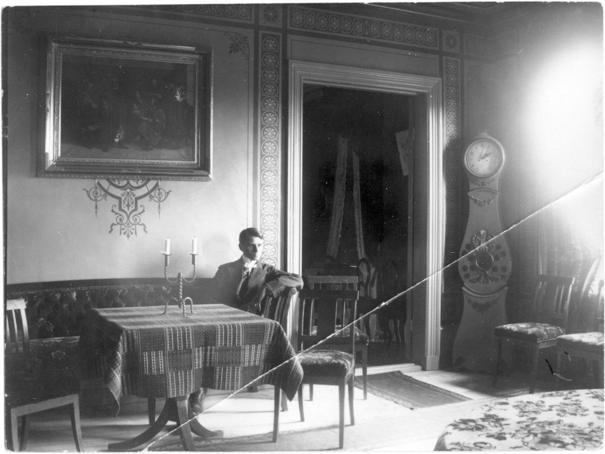 En man sitter i soffa i ett prydligt rum.