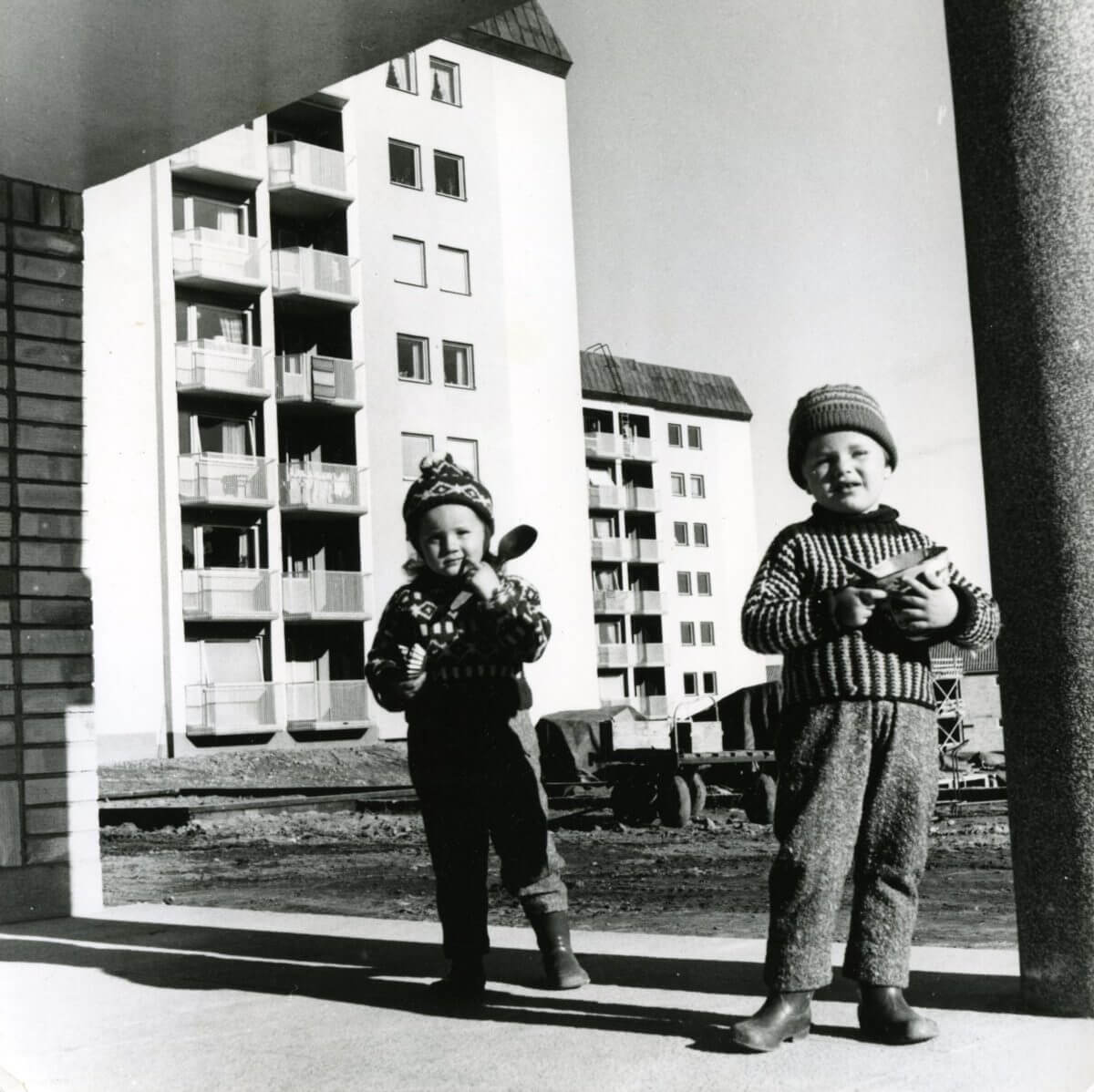 Två barn står framför några höghus.