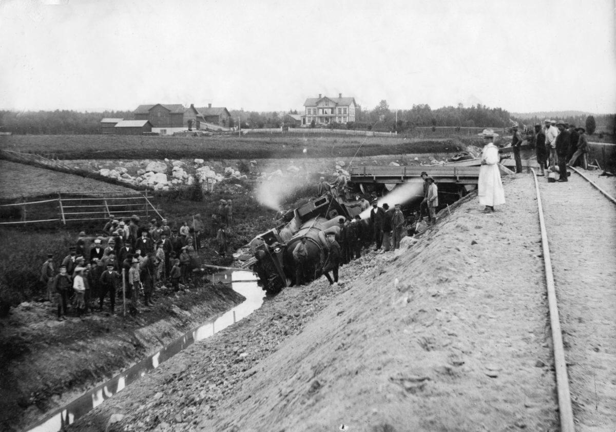 Ett urspårat tåg ligger i diket intill tågspåret. Grupper av människor står runt tåget.