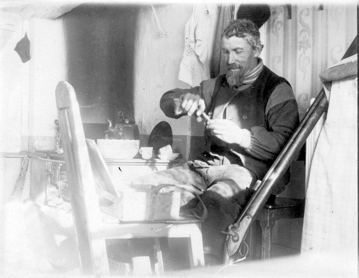 En man sittandes intill spisen laddar sin bössa.