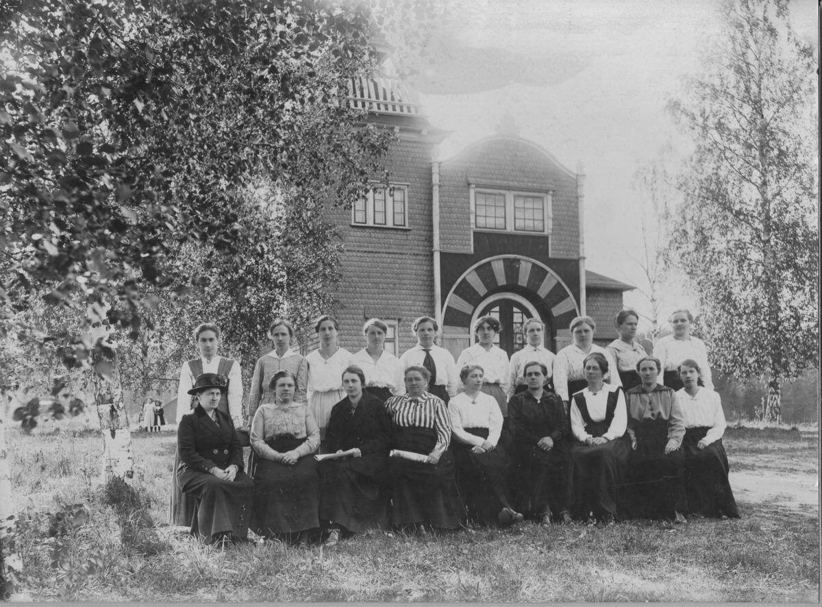 En gruppbild med kvinnor som poserar framför ett dekorativt hus.
