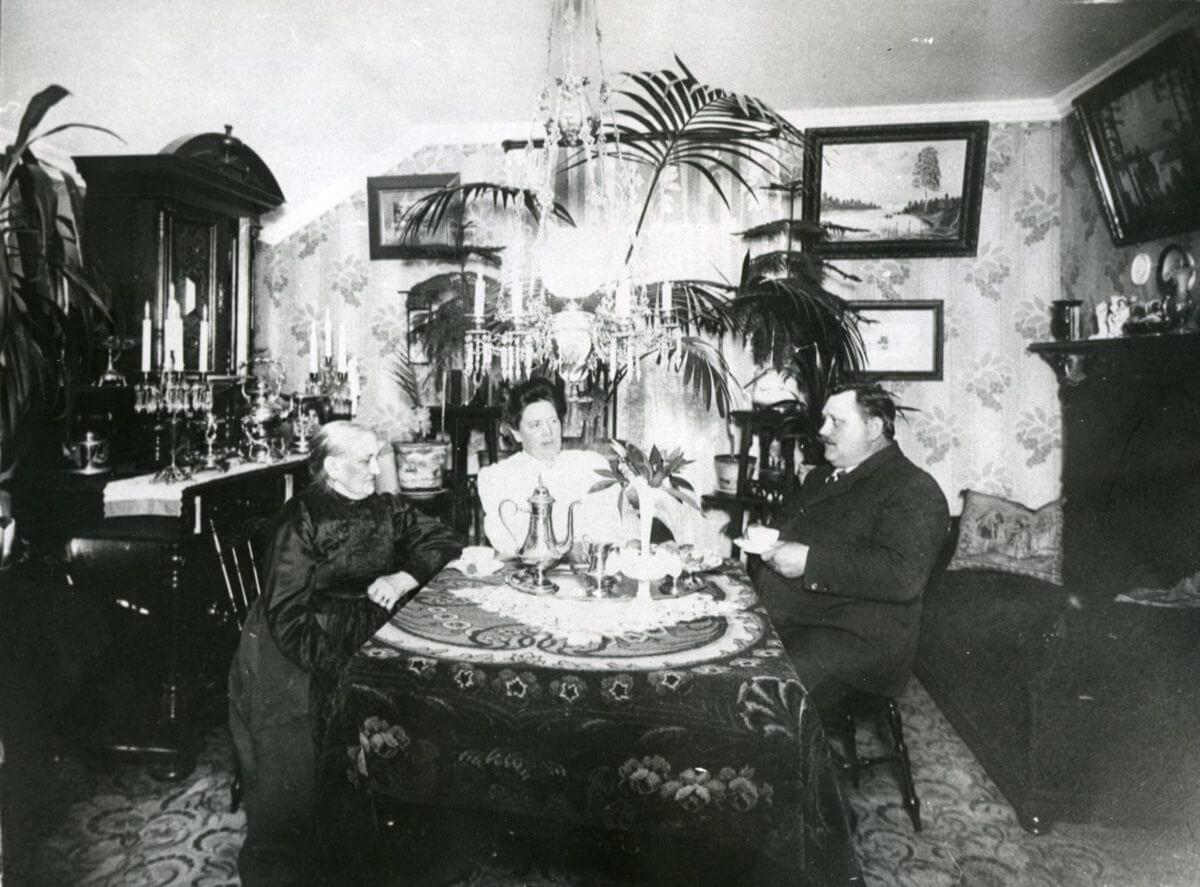 En familj äter middag vid ett fint dukat bord.