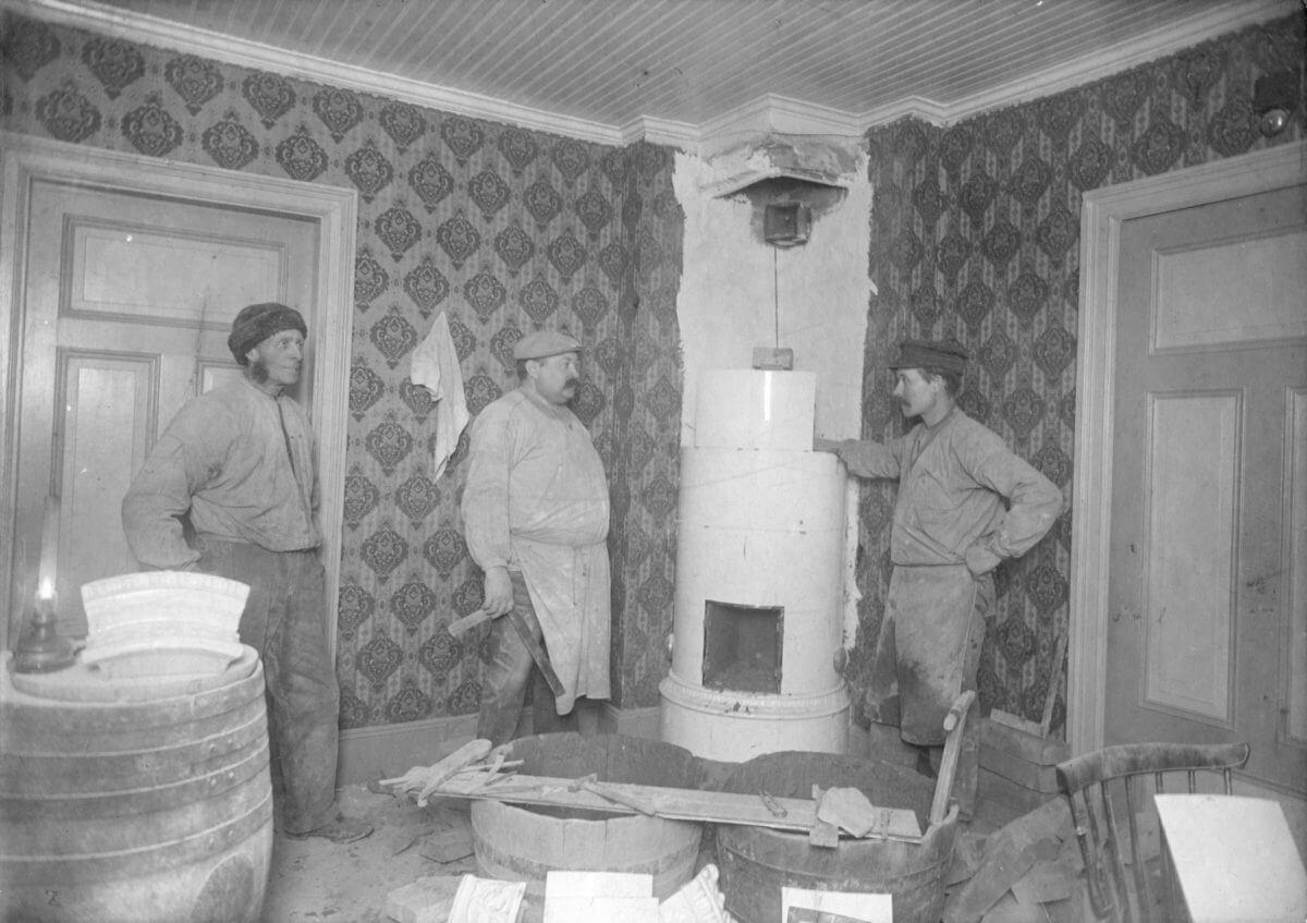 Tre män bygger en kakelugn.