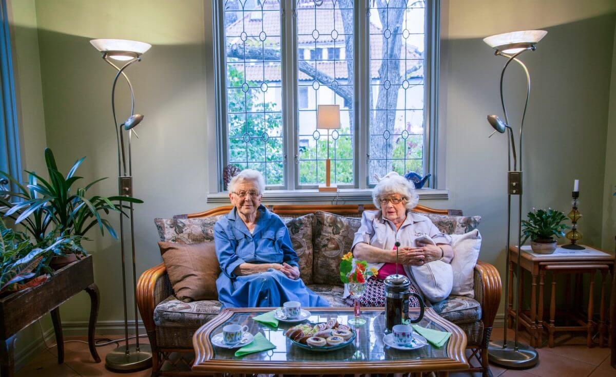 Två kvinnor sitter i en soffa bakom ett dukat fikabord.