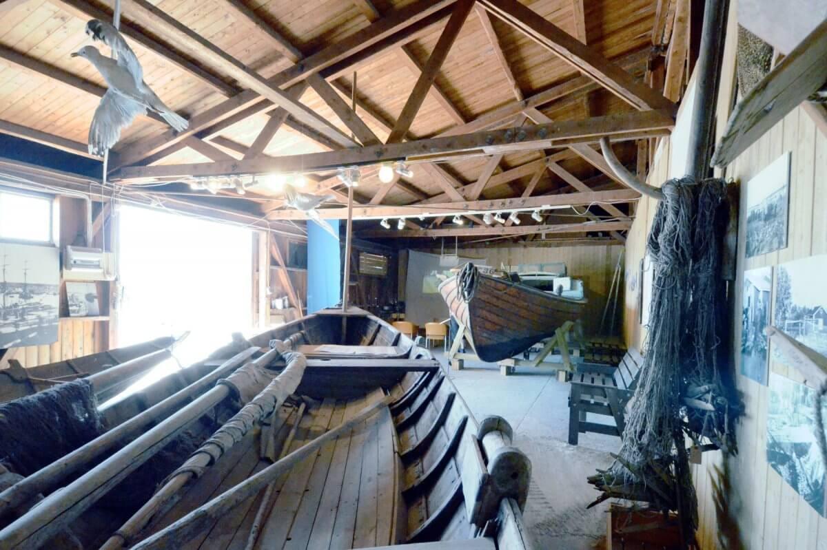 Insidan av Hälsinglands museums båtmagasin med båtar, tampar, fiskenät och bilder av fiskeläger.