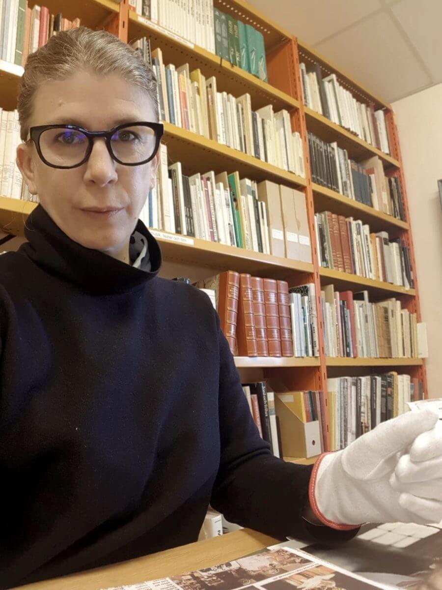 Christina Zetterlund sitter med arkivhandlingar ur Rosa Taikons arkiv i museets bibliotek