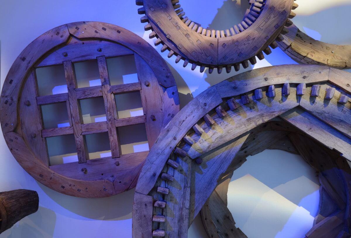 Hjul och kugghjul av trä uppsatta på vägg i utställningen De brutna mönstren..