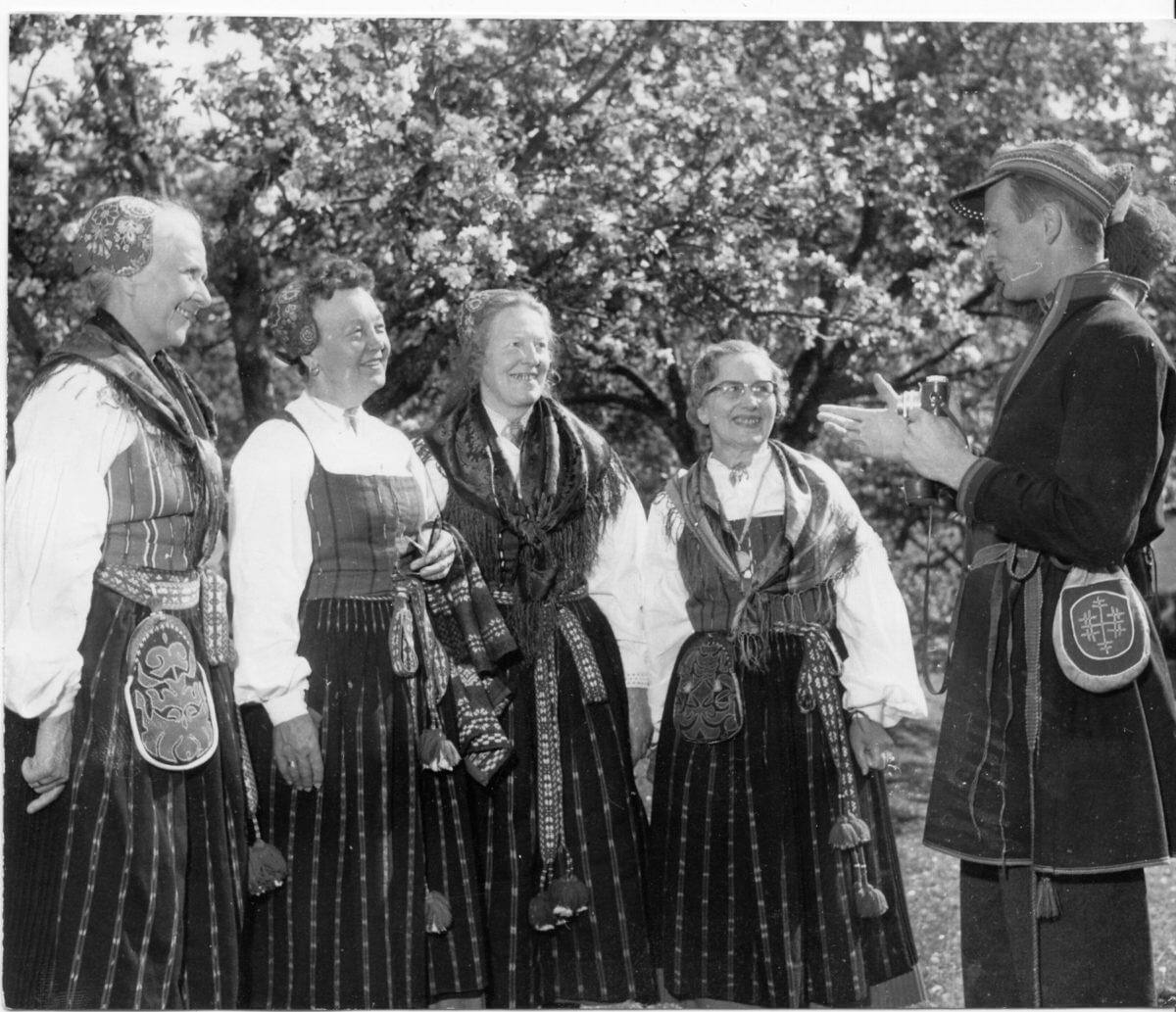 Fyra kvinnor står framför en man med kamera. Kvinnorna har folkdräkt, Delsbodräkt med sjalar, hättor och väskor. Mannen har klätt sig som en same och håller i en småbildskamera. Det är sommar och de står framför ett blommande äppelträd.