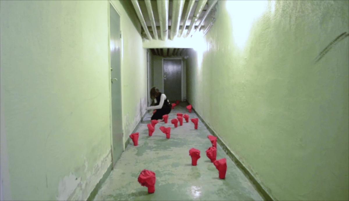 En korridor med gröna väggar och röda föremål placerade på golvet längs hela korridoren. Längs bort i korridoren sitter en kvinna på huk.