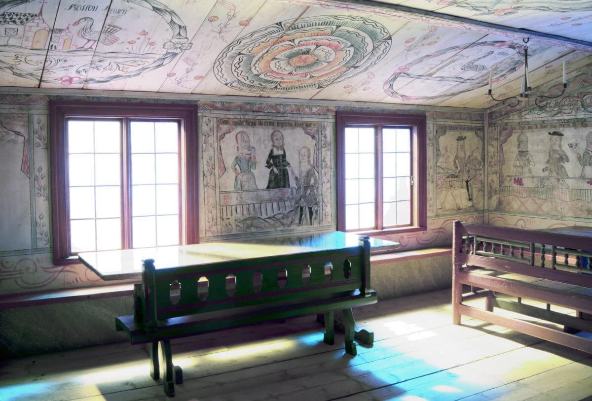 Interiör med väggmåleri och möbler i museets herrstuga.