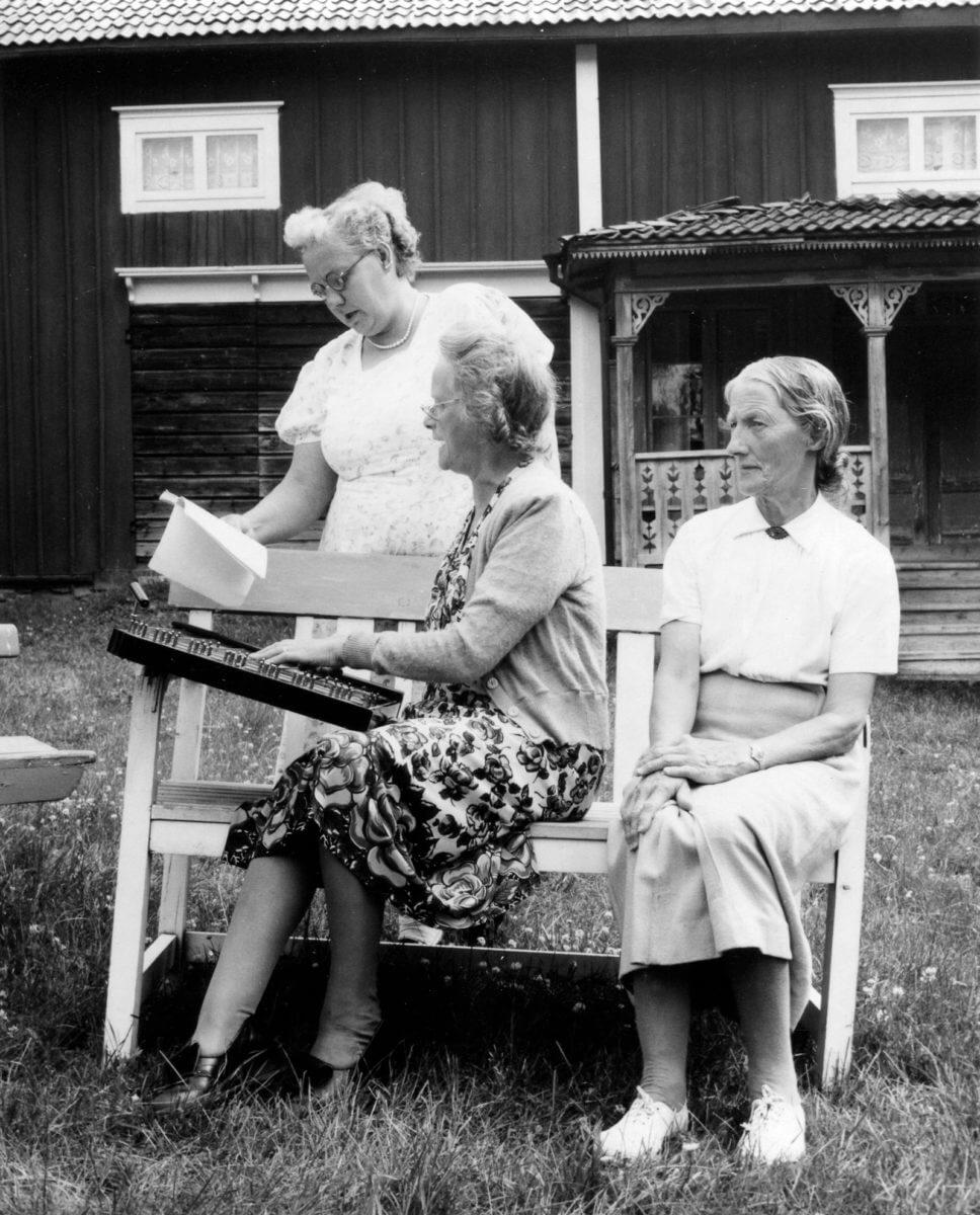 Tre kvinnor vid bänk på gårdsplan som spelar och sjunger.