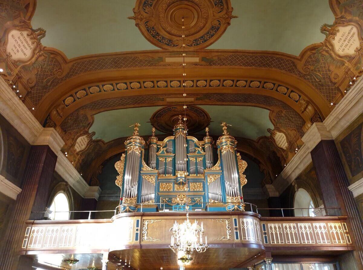 Interiör från Hudiksvalls kyrka med orgeln och dekorationsmåleriet.