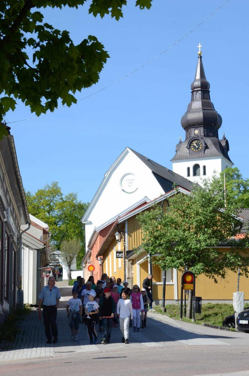 Kyrkobyggnad med gata i förgrunden.