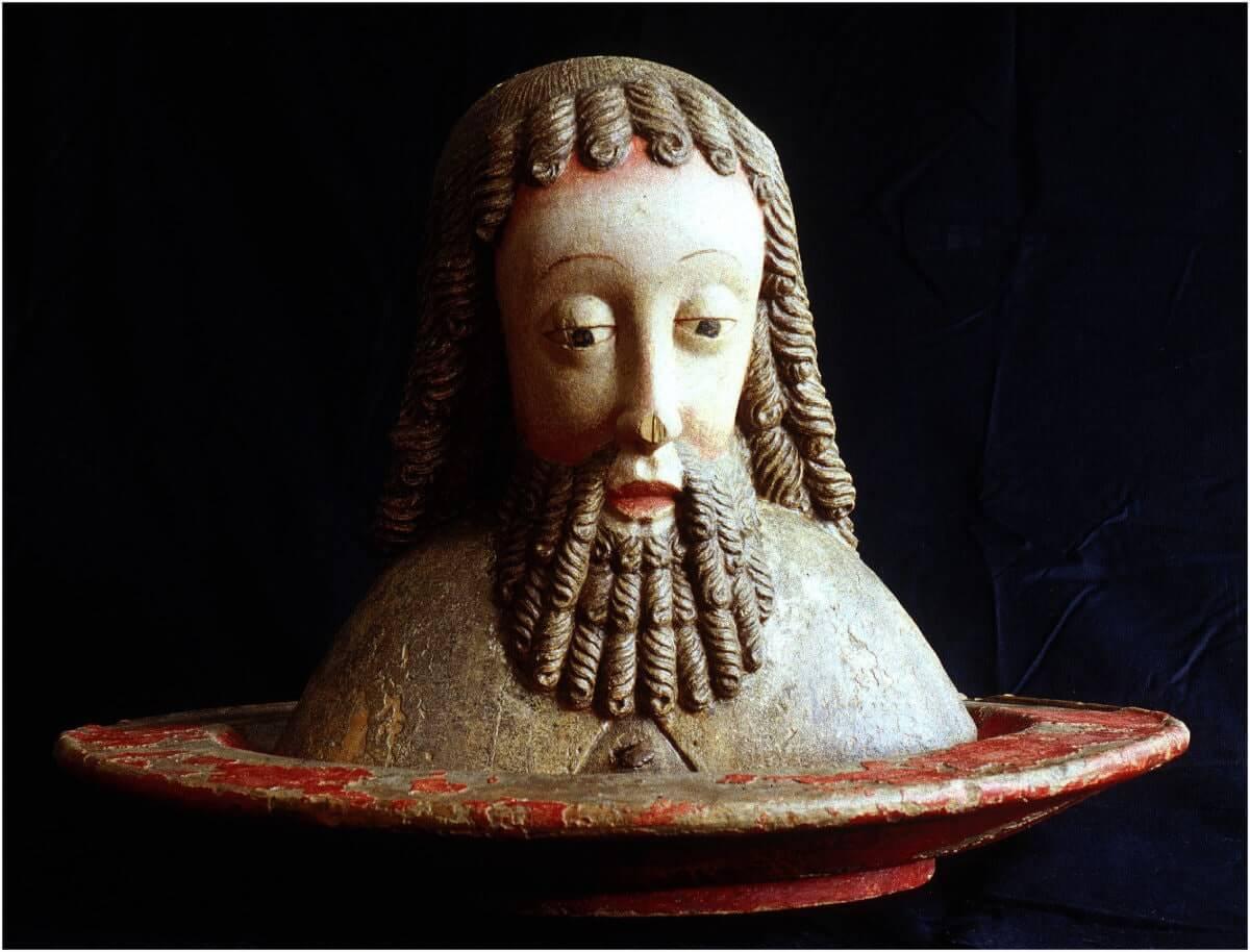Träskulptur föreställande Johannes Döparens huvud på ett fat.