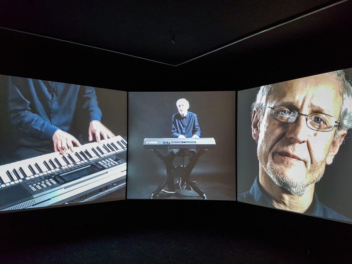 Tre projiceringar i utställning som visar intervju med musiker.