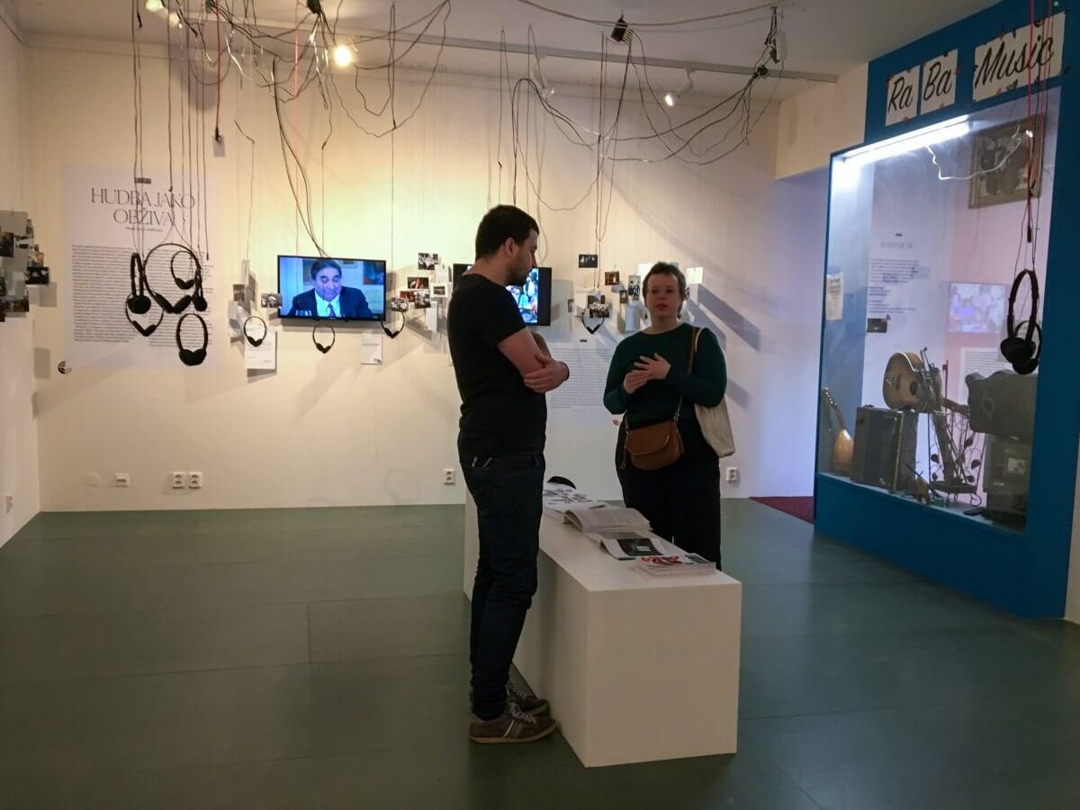 Två personer står i utställning och samtalar.