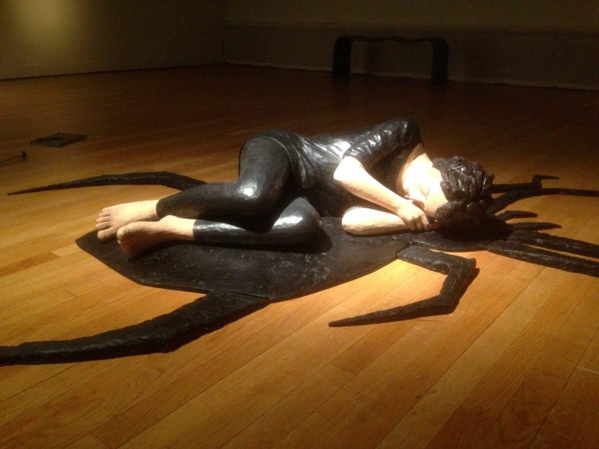 En skulptur i utställningen Metanoia föreställande en kvinna hopkrupen ovanpå en spindel.