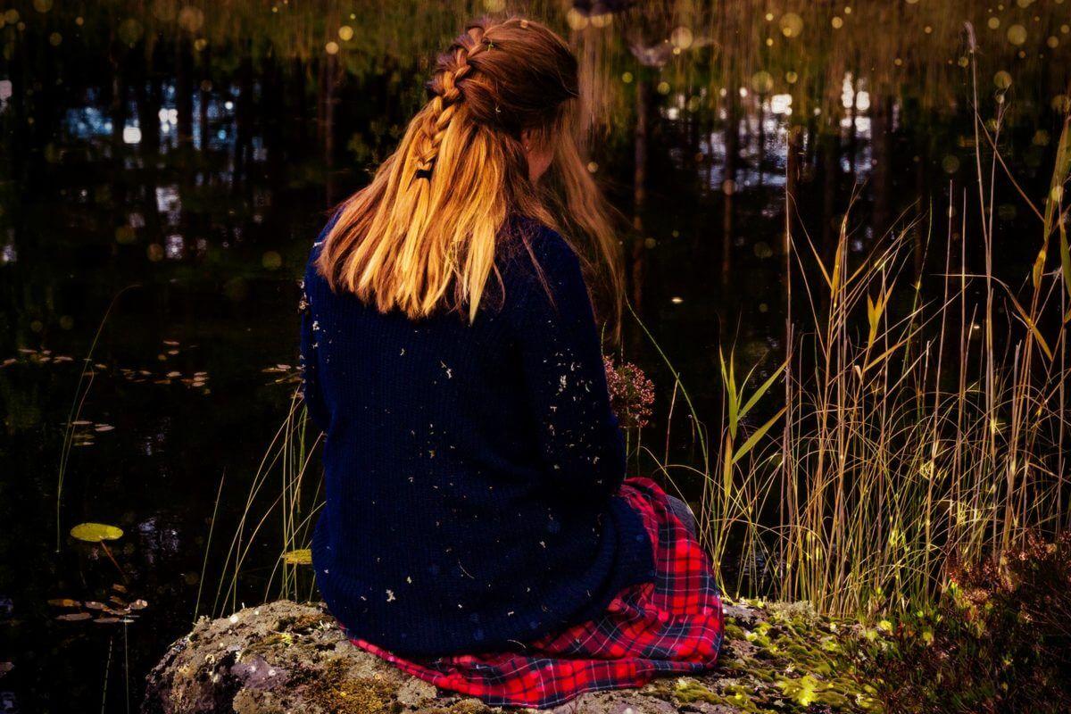Kvinna sittandes vid sjö med ryggen mot betraktaren