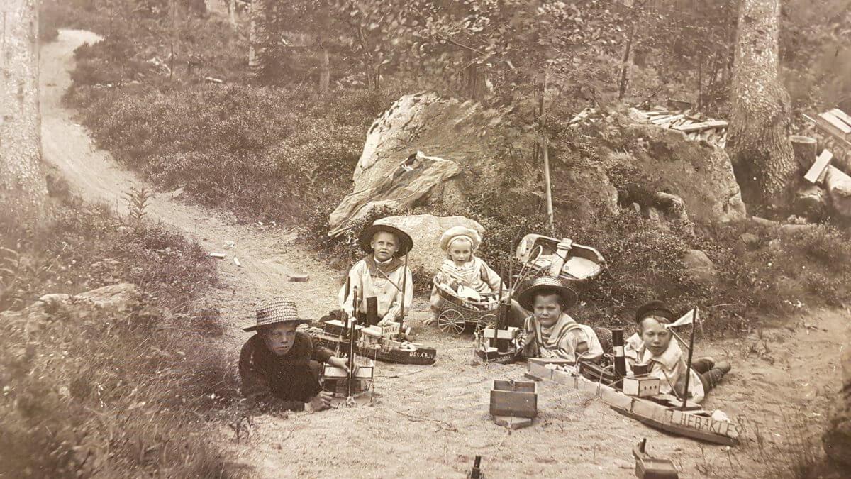 Fem barn sitter med leksaksbåtar i skogen.