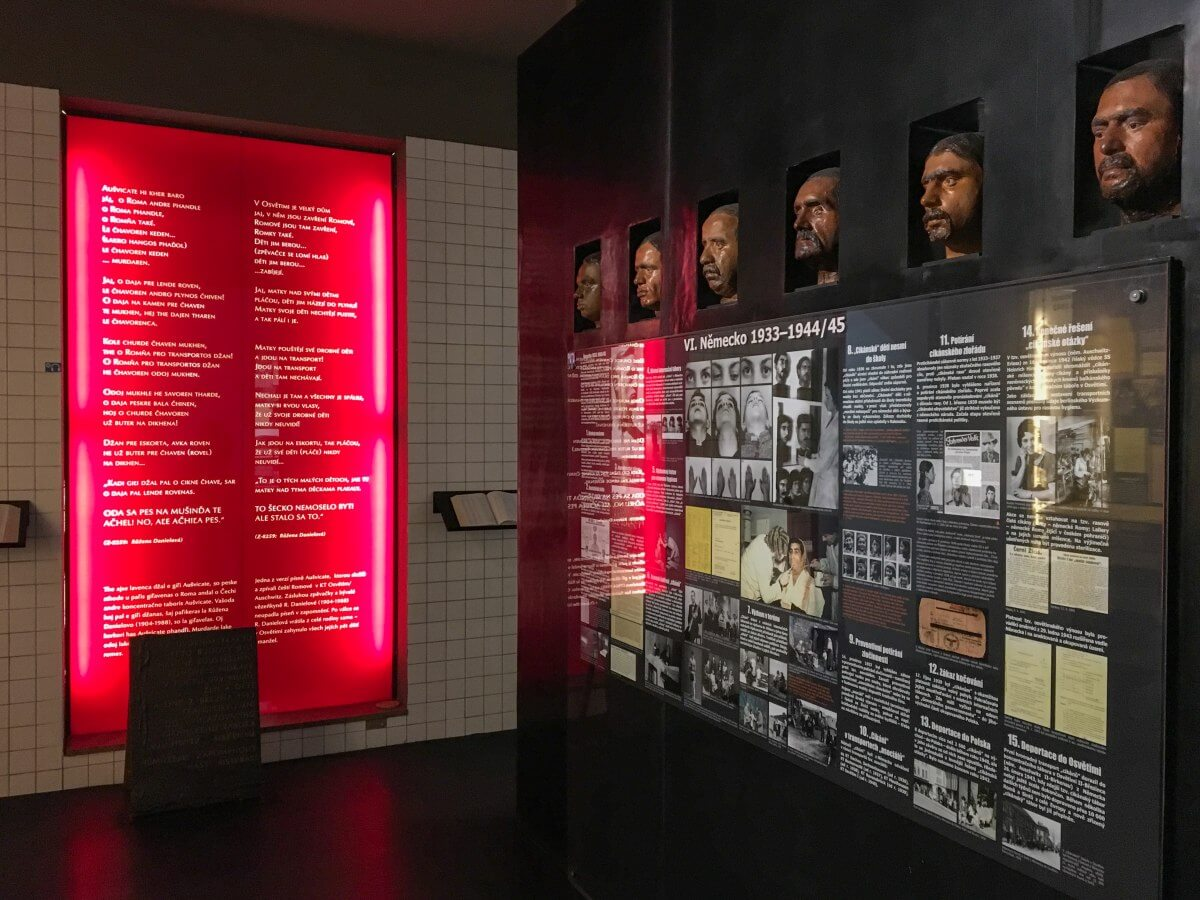 Utställningsrum med röd vepa och textvägg med ansikten