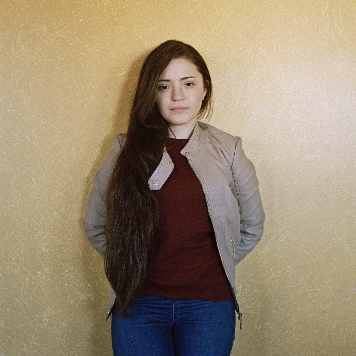 Fotografi från utställningen The End Will Be Good And Happy föreställande kvinna som lutar sig mot vägg.