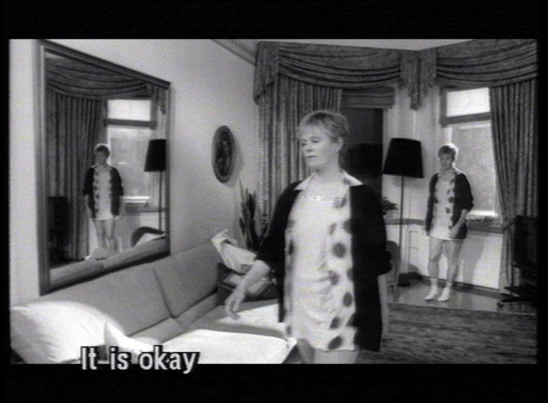 En stillbild från en film föreställande kvinna i vardagsrum.