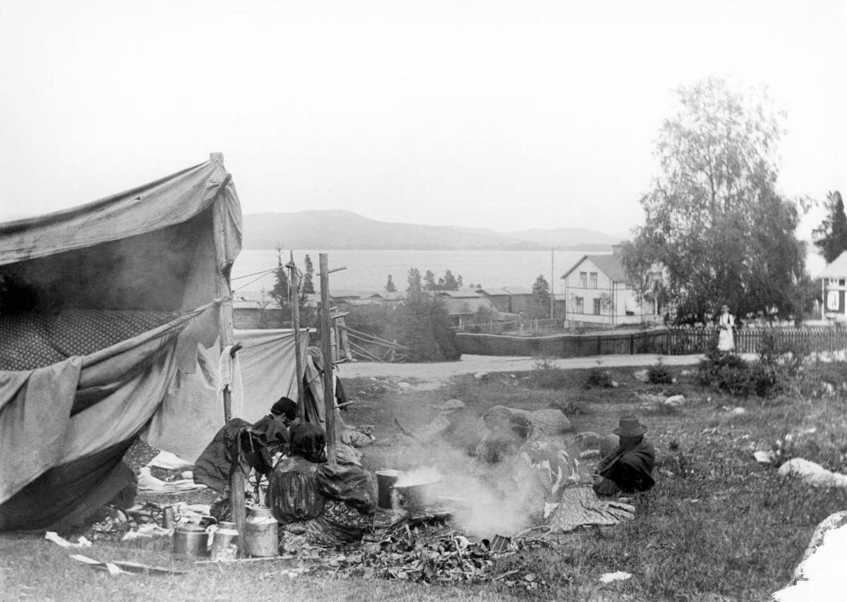 Tält med människor kring öppen eld